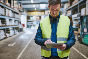 A logistics manager in a warehouse taking notes